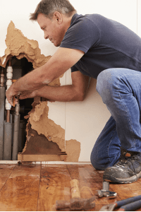 Plumber repairing burst water pipe after basement flooding