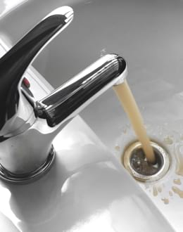 Water tap with running yellow water in a sink