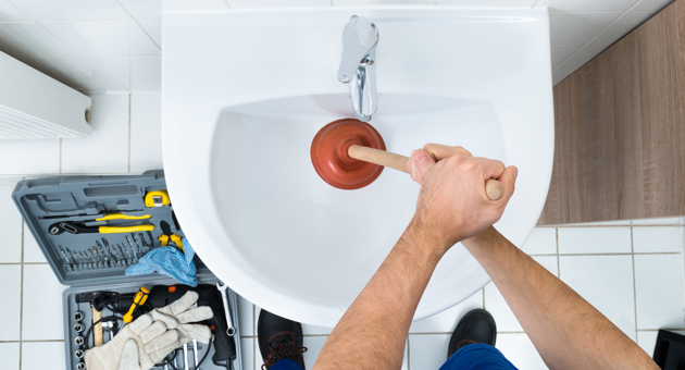 male plumber using plunger bathroom sink